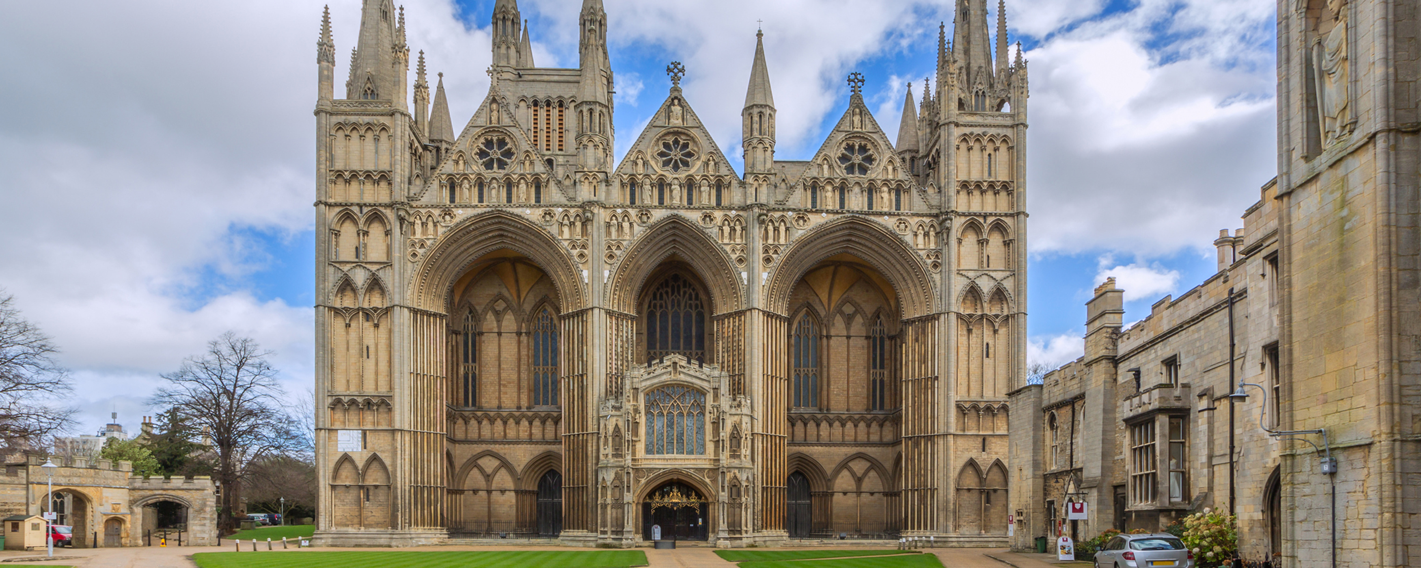 a large stone statue in front of a church with Peterborough Cathedral in the background