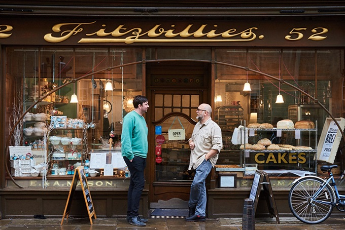 Two men standing outside Fitzbillies cake shop